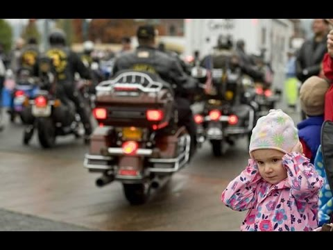 little girl holding ears at biker parade
